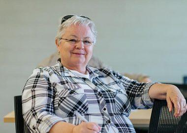 Dame âgée assise sur une chaise en souriant
