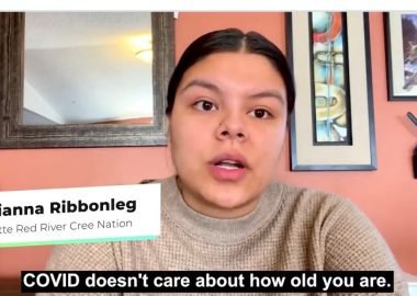 Treaty 8 youth from Southern Alberta appears in a COVID-19 Awareness video, indigenous female with black hair tied in ponytail wearing a beige sweater