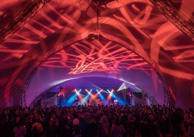 L'intérieur d'une grande tente, des lumières rouges et bleus illuminent l'estrade lors d'un concert live.