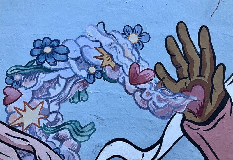 An image of a mural of a hand with a heart in its palm and flowers flowing from the heart.