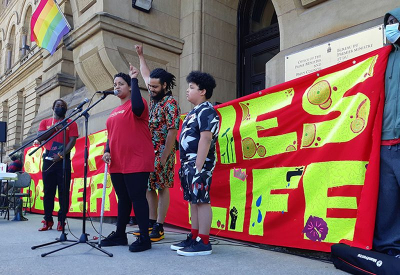 A woman stands at a microphone wo. at the door to the Prime Minister's office. Behind her, a man raises a single fist and there is a red banner that says,