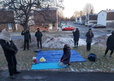 Seven protestors dressed warmly on snowy grass of a front lawn where the eviction protest took place