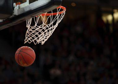 A basketball goes through a net on a court.