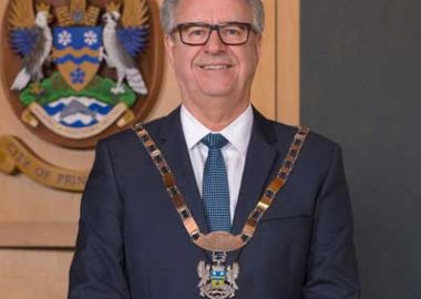 An image of Mayor Lyn Hall standing in front of the City of Prince George crest.
