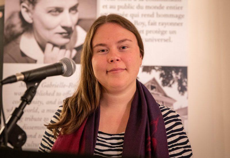 Amber est devant un micro en souriant avec un mur de photos de Gabrielle Roy en arrière plan.