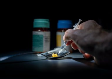 A hand holds a syringe to a spoon with two pills in it. There are two pill bottles in the background.
