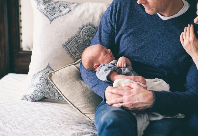 Père qui tient un bébé dans ses bras.