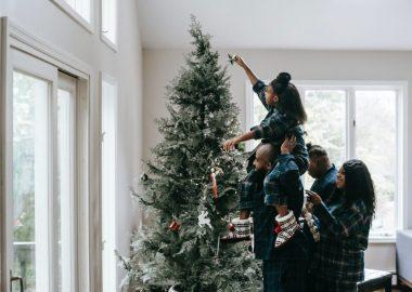 Une famille fait la décoration de leur arbre de Noël.