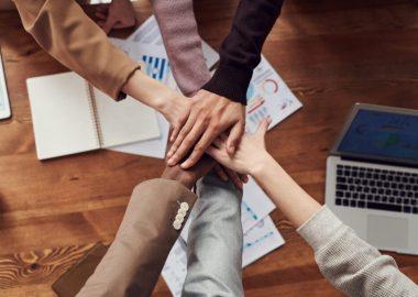 6 personnes mettant leurs mains au centre au dessus d'une table avec un ordinateur et des papiers.