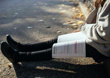 Les jambes d'une étudiante assise sur le trottoir. Un manuel de classe est ouvert sur les jambes.