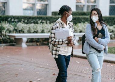Deux jeunes femmes avec masques marchant à l'extérieur.