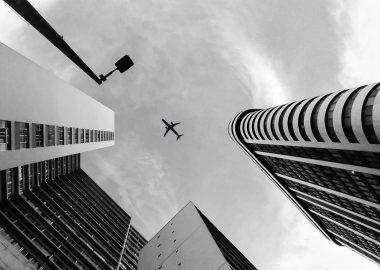 Un avion volant dans un ciel gris entouré de bâtiments.