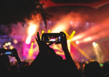 Une personne tenant son téléphone pour prendre une vidéo d'un concert