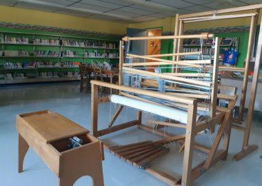 Dans une grande salle qui a des airs de bibliothèque, on aperçoit un vieux métier à tisser en bois avec un banc assorti de même couleur
