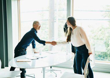 Un homme et une femme se serrant la main dans un bureau majoritairement blanc
