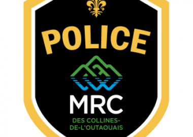 The logo of the MRC des Collines Police, with gold letters on a black background above a logo of green and blue mountains.