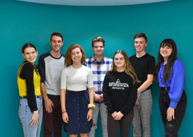 7 adolescents qui font partie de la Fédération des jeunes francophones du Nouveau-Brunswick (FJFNB) sont debout devant un arrière-plan bleu.