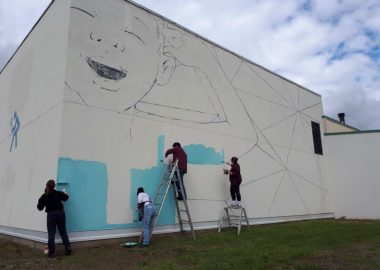 A photo of Facundo Gastiazoro and Stephanie Anderson painting a mural high on the outside wall of the recreational centre in Smithers.