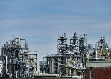 Raffinerie pétrolière où l'on observe des cheminées industrielles, des conduits et des gardes de protections.