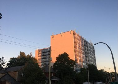 An Ottawa apartment building is seen at sunset in front of a road
