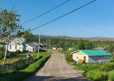Une route qui s'élonge au loin traverse un village de la Basse-Côte-Nord.