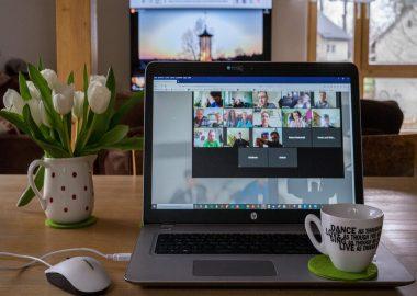 un ordinateur avec une tasse à café et des roses blanches
