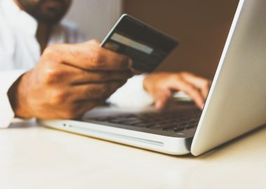 person makng online purchase on laptop, holding credit card to screen