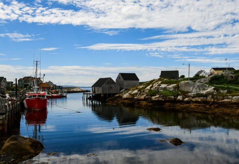 Un paysage sur l'eau avec un bateau et des habitations un peu au dessus du niveau de l'eau. Il y a du soleil et quelques nuages