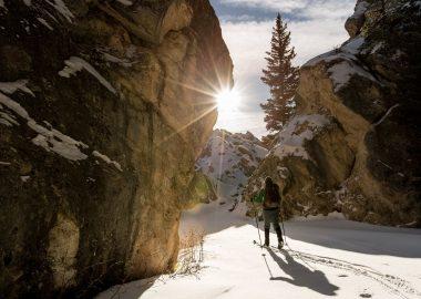 Un fondeur entre deux masses rocheuses au soleil couchant