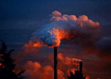 Cheminées d'usine qui libère beaucoup de fumé dans un ciel bleu et rouge