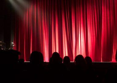 Une foule devant un grand rideau rouge dans une salle de spectacle