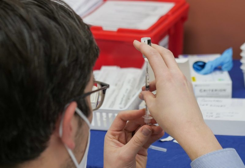 A person draws up a needle while wearing a mask.