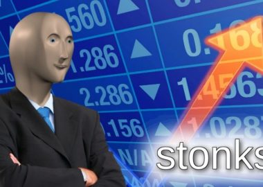 Featuring the character Meme Man standing in front of a picture representing the stock market followed by the caption