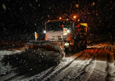 A snow plow is seen during a stowstorm at night in a stock image