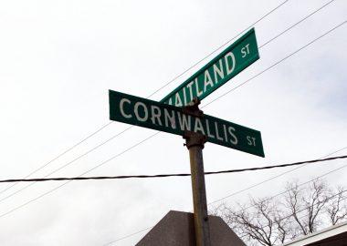 Le panneau des rues au croisement de la rue Cornwallis et Saltland. Photo prise vers le ciel, on voit des cable électrique et du ciel gris.