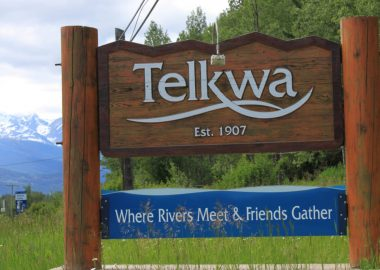 A wooden sign is beside a highway and it reads Telkwa: Where Rivers Meet and Friends Gather