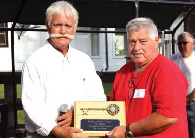 Terry Murdock, left, wearing a white collared shirt and sporting a large handlebar moustache hands an award to another man.