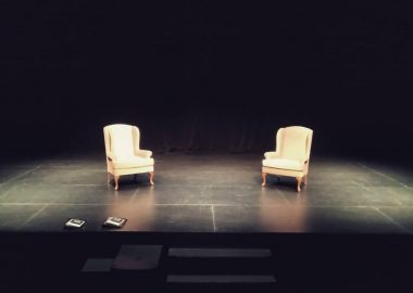 On a stage, two chairs sit side-by-side on Theatre North West's stage as they ready for a performance