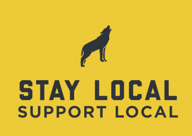 Yellow background with a silhouette of a grey wolf, text underneath reads 'Stay Local Support Local