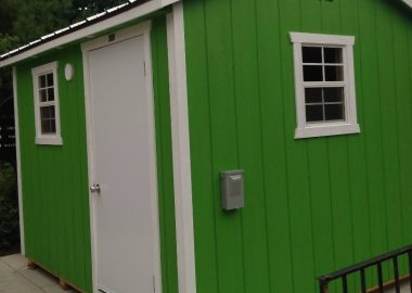 A close up of a green cabin built for the