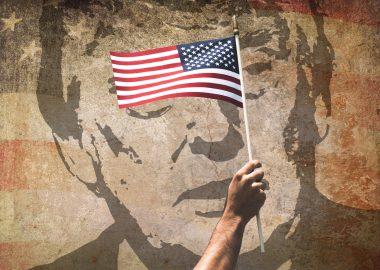 Portrait de Donald Trump derrière un drapeau américain.