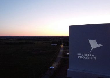 The Umbrella Projects logo is projected onto a tall outdoor building at dusk.