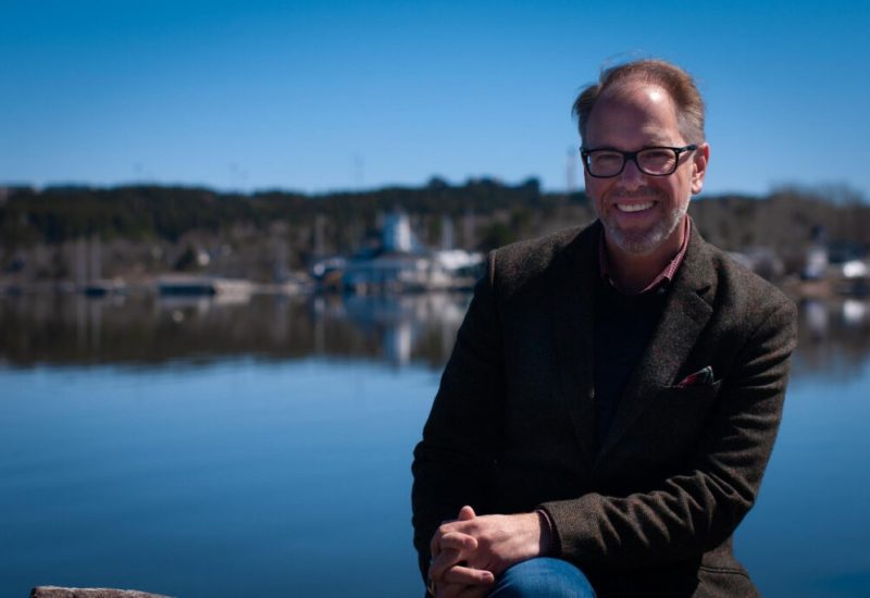 Jason Alcorn souriant assis devant une voie d'eau portant des lunettes