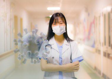 Hôpital, docteur au milieu d'un corridor d'hôpital portant un masque avec une représentation du virus à sa gauche.