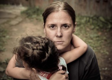 A woman hold a child trying to calm him down