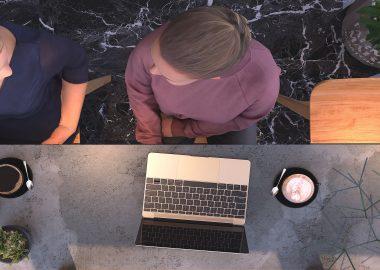 Vue de haut sur une table avec un ordinateur et deux café. Deux femmes sont attablées, l'une en chandail mauve, l'autre bleu, elles discuttent.