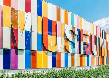 Picture of the front of the Waterloo Region museum. Greenery and grass at the bottom and blue sky above, the multicoloured wall panels with the word